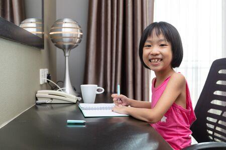 Asian Little Chinese Girl doing homework at home