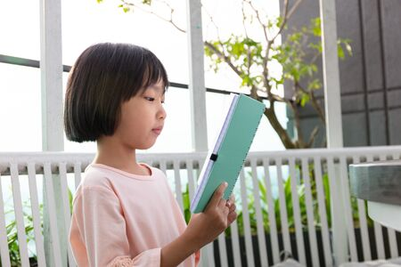Asian Little Chinese Girl reading book in the outdoor cafe
