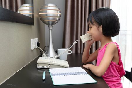 Asian Little Chinese Girl making calls at home
