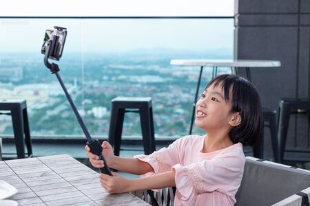 Asian Little Chinese Girl taking selfie with smartphone on selfie stick in the outdoor cafe