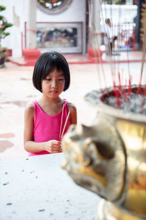 Asian Little Chinese Girl praying with burning incense sticks at a outdoor temple
