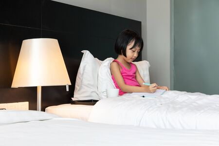 Asian Little Chinese Girl doing homework in bed at home