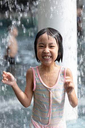 Asian Little Chinese Girl playing at water park outdoor 스톡 콘텐츠