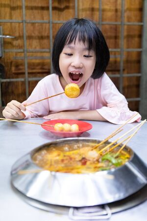 Asian Little Chinese Girl eating hot pot in a restaurant of Melaka Banque d'images