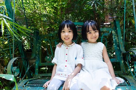 Asian Little Chinese Sisters sitting on bench at outdoor garden