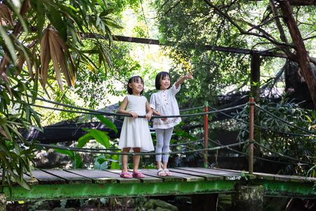 Asian Little Chinese Sisters standing on the wooden bridge at a garden 스톡 콘텐츠