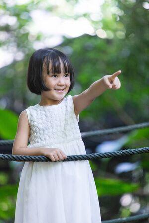 Asian Little Chinese Girl standing on a bridge at a garden