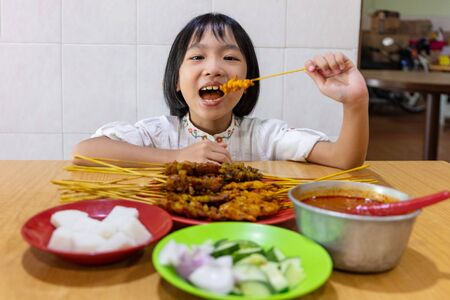 Asian Little Chinese Girl eating satay at an indoor restaurant