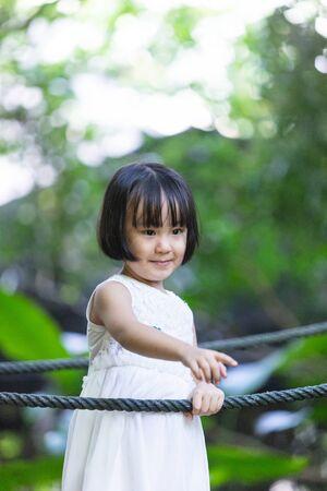 Asian Little Chinese Girl standing a bridge at a garden