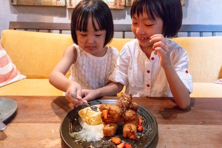Asian Little Chinese Sisters eating breakfast at an indoor cafe
