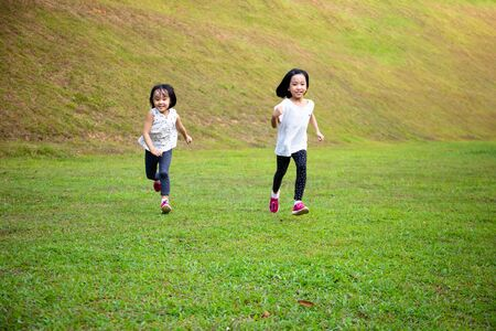 Asian Little Chinese Sisters running happily at the outdoor park