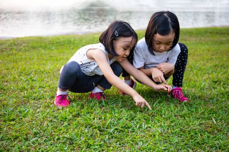 Asian Little Chinese Sisters playing at the park outdoor