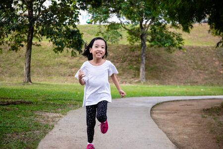 Asian Little Chinese Girl running happily at the outdoor park 스톡 콘텐츠