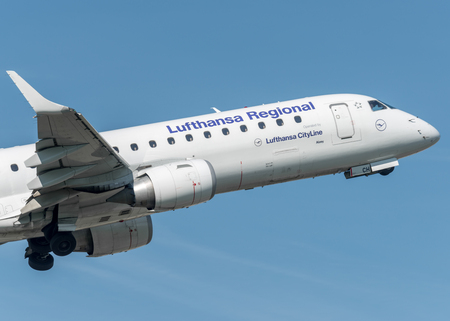 Lufthansa Regional in a blue sky of Turin, Italy Editorial