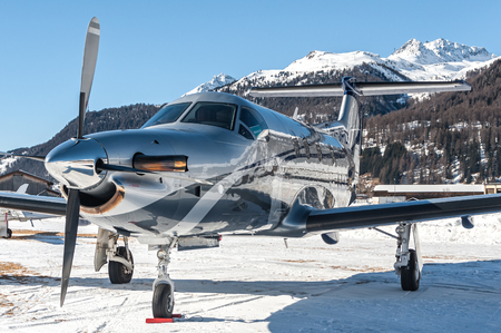 airstrip: The snow create a fantastic reflection over this PC12 on ground at Samedan Enadin Airport, Switzerland. Editorial
