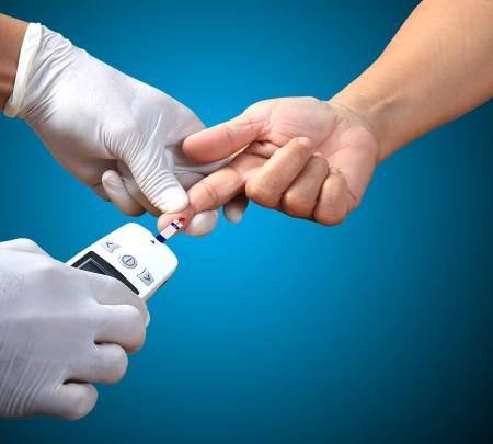 mellitus: Medico la prova di un livello di glucosio pazienti dopo che punge il dito per disegnare una goccia di sangue Archivio Fotografico