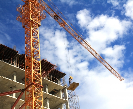 cement pile: crane and blue sky on building site ,Crane and workers at construction site against blue sky
