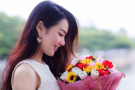 Jeune femme fleurs sentant mignons Asie Banque d'images