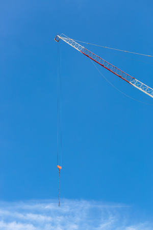 hoist: industrial crane hoist hooks and pulleys hanging by steel cables on pale blue sky. Stock Photo