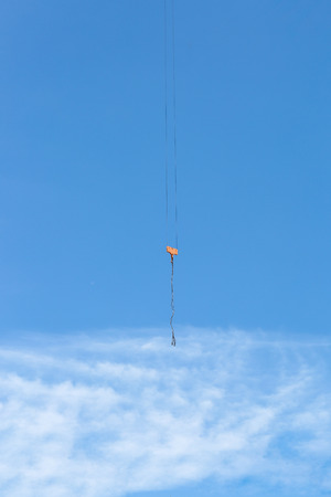 pulleys: industrial crane hoist hooks and pulleys hanging by steel cables on pale blue sky. Stock Photo