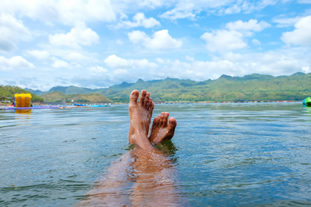 Feet and river summer landscape with trees and clouds Standard-Bild