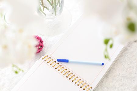 blank notebook on a white wooden table Lizenzfreie Bilder