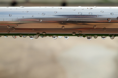Closeup of a steel tube with dew drops