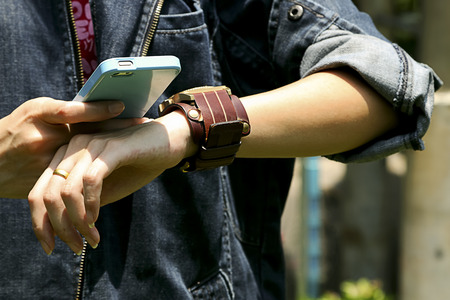 denim jacket: The people wearing a denim jacket watching smartphone and watch.