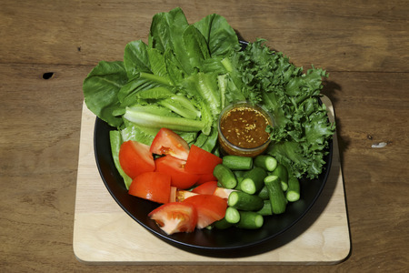 mixed vegetables: Mixed vegetables salad in black dish decorated on wooden backgroud. Stock Photo