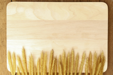 wood grass: Cutting board wood with dried grass flowers on wooden background. Stock Photo