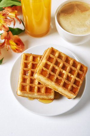 cappucino: waffles, cappucino, juice and flowers on white table