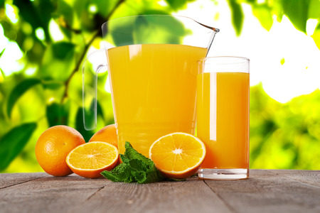 folliage: glass and pitcher with orange juice on wooden table. folliage background