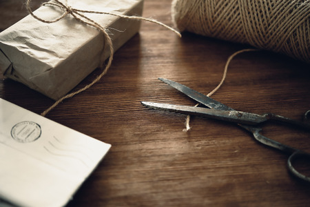 craft paper: gift box, craft paper, old rusty scissors and threads on wooden background Foto de archivo