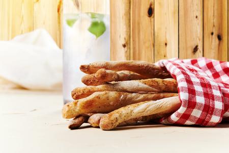 grissini. sticks of dry, crisp bread in red and white checkered napkin