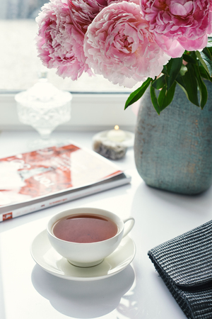 cup of black tea and pink peonies on white table