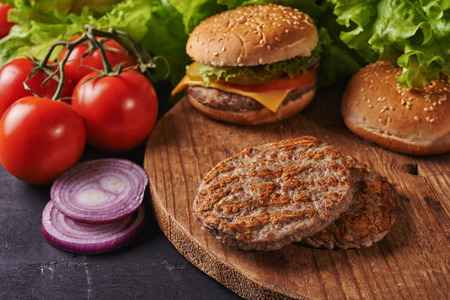 grilled patties on wooden background and burger  out of focus