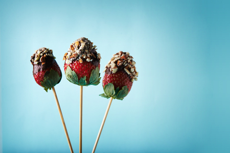 strawberries on sticks with chocolate and nuts on blue background Stok Fotoğraf - 92531284
