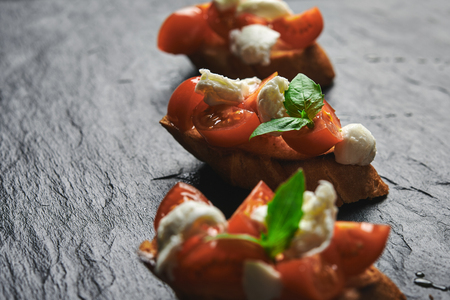 bruschetta with mozzarella and tomatoes on stone background Banque d'images