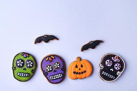 halloween cookies pumpkin, skull and bats on grey background