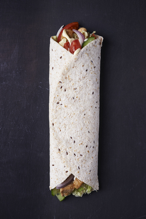 wrapped sandwich. tortilla with chicken and vegetables. top view