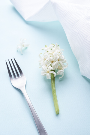 white hyacinth and silver fork on blue background