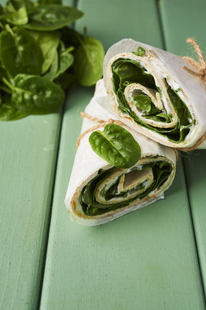 wrapped sandwiches with spinach and cream cheese on wooden background