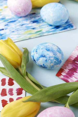 yellow tulips and painted eggs with acrilic paint texture