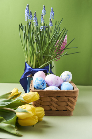 yellow tulips and painted eggs in basket