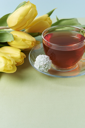 yellow tulips, candies and cup of black tea on green and blue background Stok Fotoğraf
