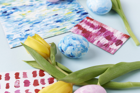 yellow tulips and painted eggs with acrilic paint