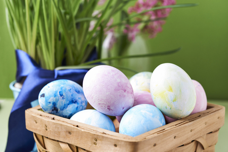 fresh flowers and painted eggs in basket