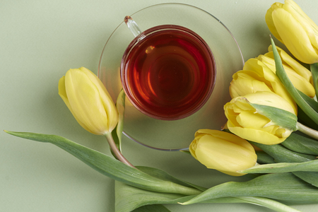 yellow tulips, and cup of black tea on green  background Stok Fotoğraf