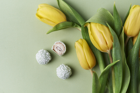coconut candies and yellow tulips. top view