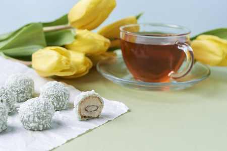 coconut candies and cup of tea and flowers